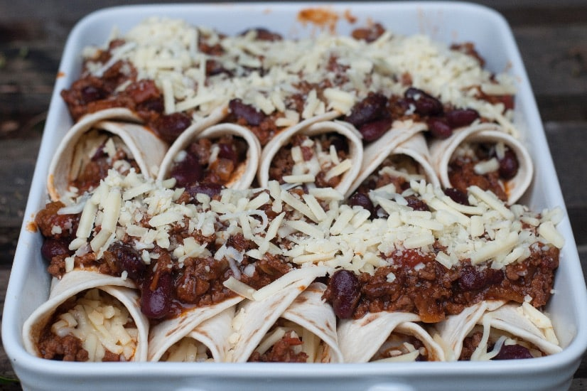 prep step topping enchiladas with cheese